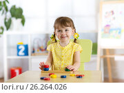 Купить «Kid girl playing with logical toy on desk in nursery room or kindergarten. Child arranging and sorting colors and sizes», фото № 26264026, снято 20 апреля 2017 г. (c) Оксана Кузьмина / Фотобанк Лори
