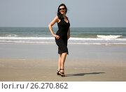 Attractive girl wearing black dress on a beach. Стоковое фото, фотограф Елена Ковалева / Фотобанк Лори