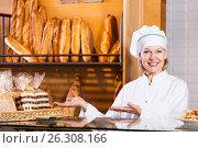 Купить «Mature woman selling fresh pastry and baguettes», фото № 26308166, снято 31 марта 2020 г. (c) Яков Филимонов / Фотобанк Лори