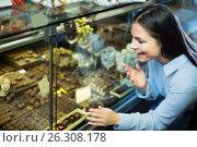 Купить «Adult girl buying chocolate», фото № 26308178, снято 21 февраля 2020 г. (c) Яков Филимонов / Фотобанк Лори