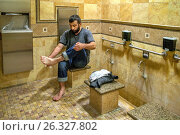 Купить «A Muslim man at an Anaheim, CA, mosque performs ritual ablutions as he ceremonially washes his feet in a specialized men's restroom as a sign of reverence before participating in afternoon prayers.», фото № 26327802, снято 23 октября 2016 г. (c) age Fotostock / Фотобанк Лори
