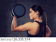 Купить «young woman flexing muscles with dumbbells in gym», фото № 26335574, снято 12 декабря 2015 г. (c) Syda Productions / Фотобанк Лори
