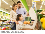 Купить «family weighing oranges on scale at grocery store», фото № 26335762, снято 21 октября 2016 г. (c) Syda Productions / Фотобанк Лори
