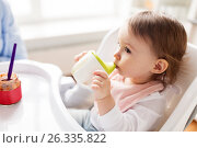 Купить «baby drinking from spout cup in highchair at home», фото № 26335822, снято 24 января 2017 г. (c) Syda Productions / Фотобанк Лори