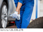 Купить «mechanic with screwdriver changing car tire», фото № 26336278, снято 1 июля 2016 г. (c) Syda Productions / Фотобанк Лори