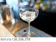 Купить «glass with ice cube at cocktail bar», фото № 26336378, снято 7 февраля 2017 г. (c) Syda Productions / Фотобанк Лори