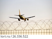 Купить «Самолёт улетает на закате вдаль за забор с колючей проволокой», фото № 26336522, снято 13 мая 2017 г. (c) Максим Мицун / Фотобанк Лори