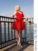 Купить «Молодая девушка стоит на набережной реки в красном платье», фото № 26338202, снято 14 мая 2017 г. (c) Момотюк Сергей / Фотобанк Лори