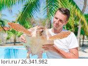 Купить «Tourist man with sea turtle in the hands in exotic reserve», фото № 26341982, снято 10 апреля 2017 г. (c) Дмитрий Травников / Фотобанк Лори