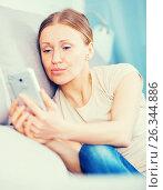Купить «Worried woman on couch with phone», фото № 26344886, снято 12 апреля 2017 г. (c) Яков Филимонов / Фотобанк Лори