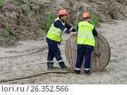 Two workers pulling roll high voltage cable line (2016 год). Редакционное фото, фотограф Сергей Буторин / Фотобанк Лори