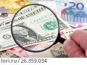 Купить «Лупа в руке фокусируется на долларе в окружении европейских валют», фото № 26359034, снято 12 июля 2009 г. (c) Александр Гаценко / Фотобанк Лори