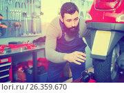 Купить «Male worker fixing failed scooter in workshop», фото № 26359670, снято 25 сентября 2018 г. (c) Яков Филимонов / Фотобанк Лори