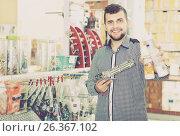 Купить «Smiling man customers choosing on best glue gun», фото № 26367102, снято 5 апреля 2017 г. (c) Яков Филимонов / Фотобанк Лори