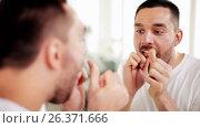 Купить «man with dental floss cleaning teeth at bathroom», видеоролик № 26371666, снято 20 января 2020 г. (c) Syda Productions / Фотобанк Лори