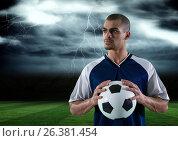 Купить «soccer player with ball on his hand in the field. storm», фото № 26381454, снято 24 июня 2019 г. (c) Wavebreak Media / Фотобанк Лори