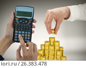 Cropped image of hands working on calculator and arranging gold coins. Стоковое фото, агентство Wavebreak Media / Фотобанк Лори