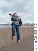 Фотограф снимает, сидя на парапете Петровской набережной. Санкт-Петербург, Россия (2017 год). Редакционное фото, фотограф Виктор Карасев / Фотобанк Лори