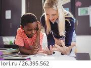 Купить «Teacher helping schoolgirl with her homework in classroom», фото № 26395562, снято 11 марта 2017 г. (c) Wavebreak Media / Фотобанк Лори
