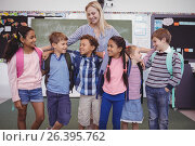 Купить «Happy teacher standing with schoolkid in classroom», фото № 26395762, снято 11 марта 2017 г. (c) Wavebreak Media / Фотобанк Лори