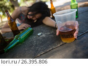 Купить «Drunken woman sleeping on the table and holding a glass of beer», фото № 26395806, снято 9 марта 2017 г. (c) Wavebreak Media / Фотобанк Лори