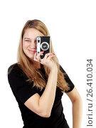 Купить «Молодая девушка на белом фоне фотографирует», фото № 26410034, снято 7 декабря 2013 г. (c) Александр Гаценко / Фотобанк Лори