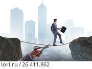 Купить «Hand cutting the rope under businessman tightrope walker», фото № 26411862, снято 30 мая 2020 г. (c) Elnur / Фотобанк Лори
