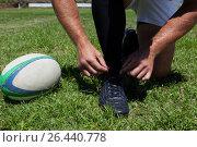 Купить «Rugby player tying shoes on field», фото № 26440778, снято 9 февраля 2017 г. (c) Wavebreak Media / Фотобанк Лори