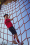 Boy climbing a net during obstacle course training, фото № 26448714, снято 16 марта 2017 г. (c) Wavebreak Media / Фотобанк Лори