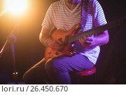 Купить «Mid section of singer playing guitar in nightclub», фото № 26450670, снято 7 марта 2017 г. (c) Wavebreak Media / Фотобанк Лори