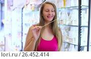 Купить «girl choose passion perfume in cosmetics shop», видеоролик № 26452414, снято 16 мая 2017 г. (c) Яков Филимонов / Фотобанк Лори