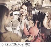 Купить «Female seller demonstrating client bras in underwear store», фото № 26452782, снято 20 марта 2017 г. (c) Яков Филимонов / Фотобанк Лори