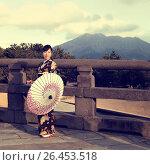 Купить «Японская девушка в кимоно и с зонтом стоит на историческом мосту на фоне вулкана», фото № 26453518, снято 30 января 2011 г. (c) Александр Гаценко / Фотобанк Лори