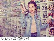 Купить «Portrait of girl choosing paint color in aerosol can in art shop», фото № 26456070, снято 12 апреля 2017 г. (c) Яков Филимонов / Фотобанк Лори