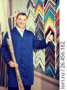Купить «portrait of man in uniform choosing framing moulding in studio», фото № 26456182, снято 20 августа 2018 г. (c) Яков Филимонов / Фотобанк Лори
