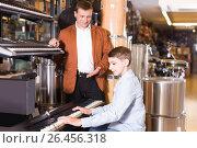 Купить «Father and teenage son examining keyboards in guitar shop», фото № 26456318, снято 29 марта 2017 г. (c) Яков Филимонов / Фотобанк Лори