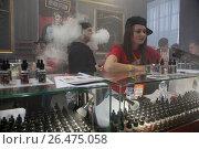 Купить «Продавцы за прилавком в магазине курительных смесей продают разные сорта жидкостей для электронных сигарет на выставке Vape Show в городе Москве,  Россия», фото № 26475058, снято 22 апреля 2017 г. (c) Николай Винокуров / Фотобанк Лори