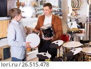 Купить «Father and teenage son examining drum units in guitar shop», фото № 26515478, снято 29 марта 2017 г. (c) Яков Филимонов / Фотобанк Лори