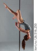 Купить «Beautiful pose of an athlete on a pylon, on a gray background», фото № 26516250, снято 19 марта 2017 г. (c) Константин Лабунский / Фотобанк Лори