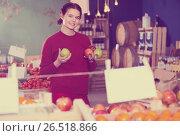 Купить «Portrait of positive brunette girl buying apple in supermarket», фото № 26518866, снято 1 марта 2017 г. (c) Яков Филимонов / Фотобанк Лори