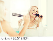 Купить «happy woman singing to hair brush at bathroom», фото № 26519834, снято 13 февраля 2016 г. (c) Syda Productions / Фотобанк Лори