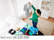 Купить «woman packing travel bag at home or hotel room», фото № 26520090, снято 18 января 2017 г. (c) Syda Productions / Фотобанк Лори