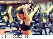 Купить «young woman flexing muscles with dumbbell in gym», фото № 26520198, снято 12 декабря 2015 г. (c) Syda Productions / Фотобанк Лори