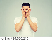 Купить «man in white t-shirt covering his face with hands», фото № 26520210, снято 15 января 2016 г. (c) Syda Productions / Фотобанк Лори