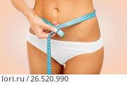 Купить «close up of woman body with measure tape on waist», фото № 26520990, снято 9 апреля 2017 г. (c) Syda Productions / Фотобанк Лори