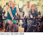 Купить «People cycling in a gym», фото № 26541954, снято 19 июля 2018 г. (c) Яков Филимонов / Фотобанк Лори