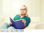 Купить «young woman in glasses reading book at home», фото № 26546594, снято 7 февраля 2016 г. (c) Syda Productions / Фотобанк Лори