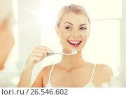Купить «woman with toothbrush cleaning teeth at bathroom», фото № 26546602, снято 13 февраля 2016 г. (c) Syda Productions / Фотобанк Лори