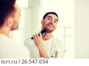 Купить «man shaving beard with trimmer at bathroom», фото № 26547034, снято 15 января 2016 г. (c) Syda Productions / Фотобанк Лори