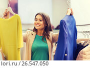 Купить «happy young woman choosing clothes in mall», фото № 26547050, снято 19 февраля 2016 г. (c) Syda Productions / Фотобанк Лори